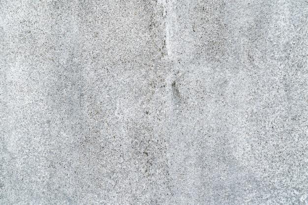 Geschlossen herauf strukturierten hintergrund der grauen betonmauer des schmutzes.