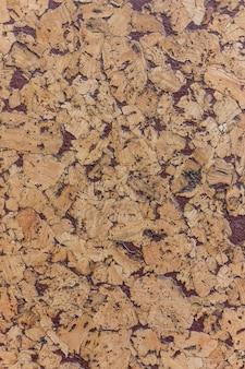 Geschlossen von braunem korkholzbrettbeschaffenheitshintergrund mit purpur