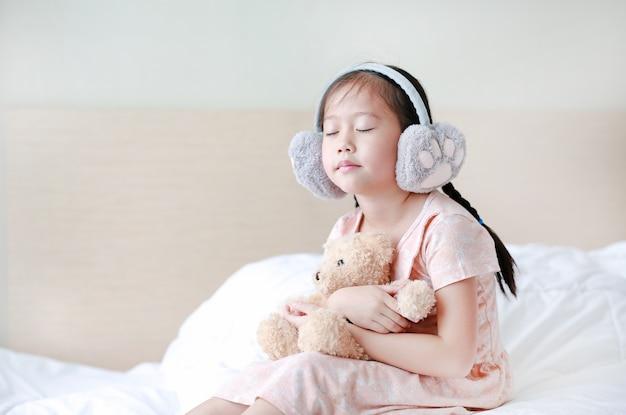 Geschlossene augen kleines asiatisches kindermädchen, das winterohrenschützer trägt und teddybären beim auf dem bett zu hause sitzen umfasst.