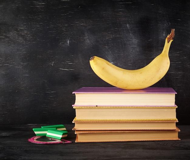 Geschlossene bücher mit gelben blättern und reifer banane