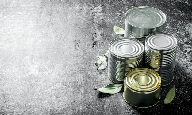 Geschlossene dosen mit konserven. auf dunklem rustikalem hintergrund