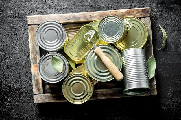 Geschlossene dosen mit konserven auf einem holztablett. auf schwarzem rustikalem hintergrund