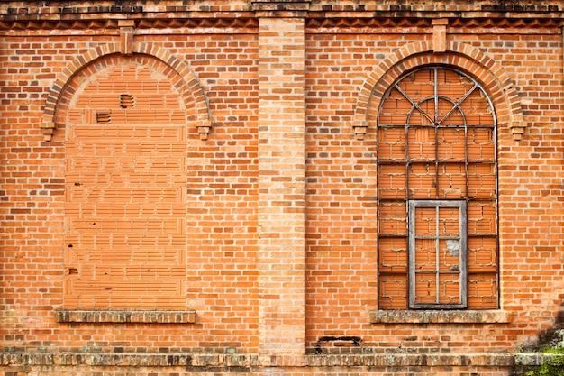 Geschlossene fenster in der alten orangefarbenen backsteinmauer