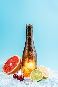 Geschlossene flasche braunes glasbier auf eis. früchte liegen in der nähe. konzept von obst craft bier oder apfelwein