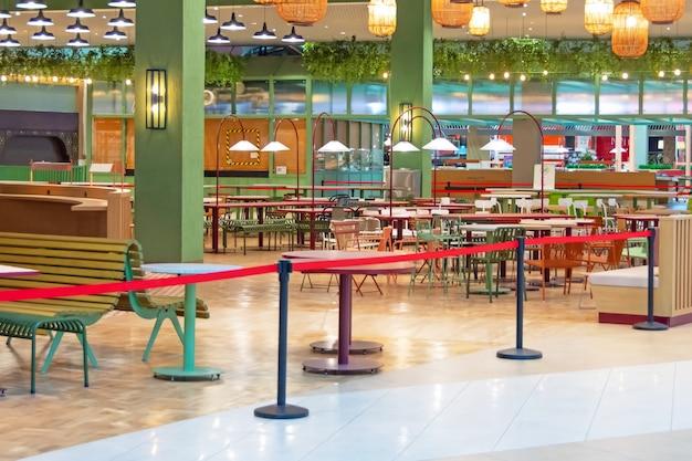 Geschlossene food courts leeren tische und stühle in catering- und fast-wood-bereichen, die durch ein rotes flugdeck versiegelt und eingezäunt sind. ausbruch des coronavirus.
