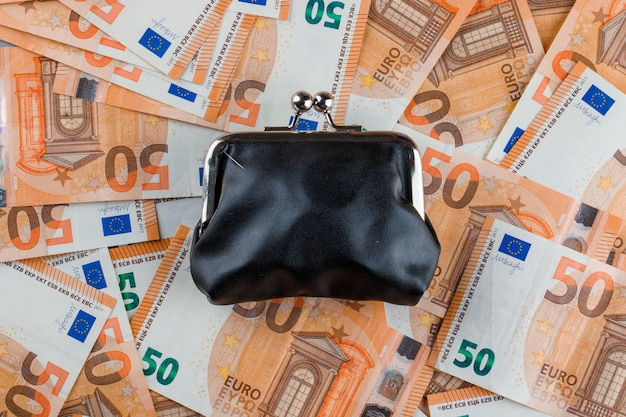 Geschlossene geldbörse auf banknotentisch.