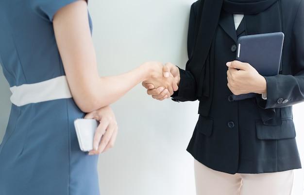 Geschlossene hand betrügt von zwei frauen eine in muslimischen hijab hand halten tablette ein kleid in modernen anzug hand halten smartphone, erfolg geschäftskonzept.