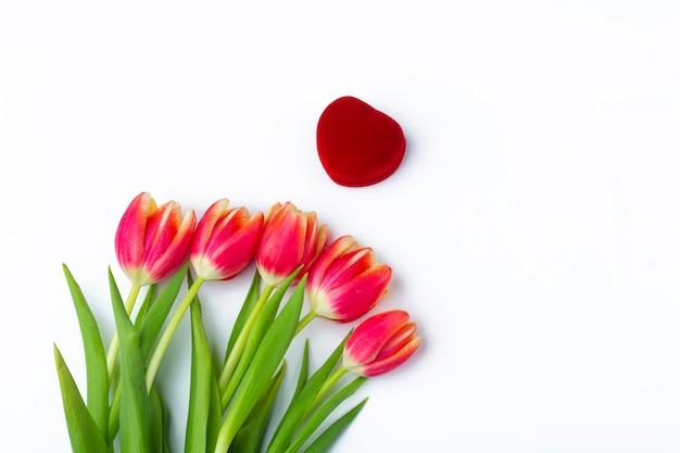 Geschlossene herzförmige ringschachtel aus rotem samt und strauß aus fünf frischen roten tulpen auf weiß