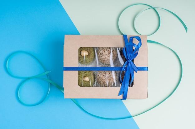 Geschlossene kartonschachtel mit einer auswahl an veganen nuss-trüffeln auf buntem blauem und grünem hintergrund