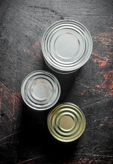 Geschlossene metalldosen mit konserven auf dunklem rustikalem tisch