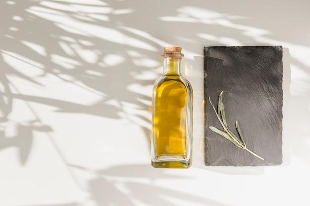 Geschlossene olivenölflasche und -zweig auf steinplatte über dem normalen hintergrund