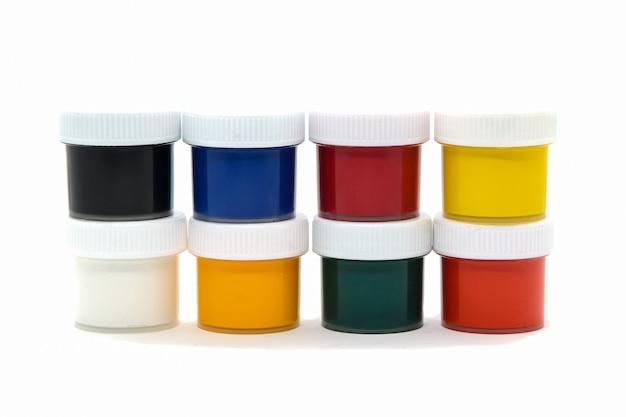 Geschlossene plastikgläser mit gouachefarbe in verschiedenen farben für die kreativität der kinder auf weiß