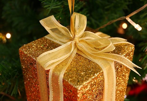 Geschlossene quadratische mini-geschenkbox aus gold mit goldener schleife