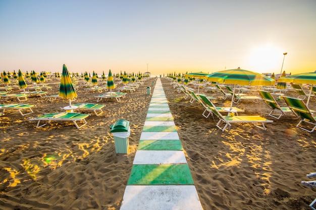 Geschlossene sonnenschirme und liegestühle am strand