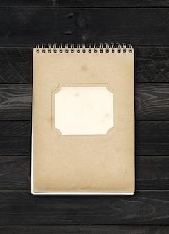 Geschlossene spirale notizbuch mit leerem etikett auf einem schwarzen holztisch. attrappe, lehrmodell, simulation