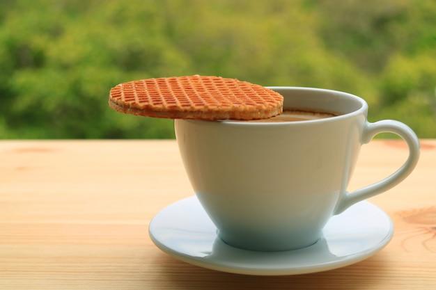 Geschlossene stroopwafel, die auf die schale des heißen kaffees gesetzt wurde, diente auf holztisch