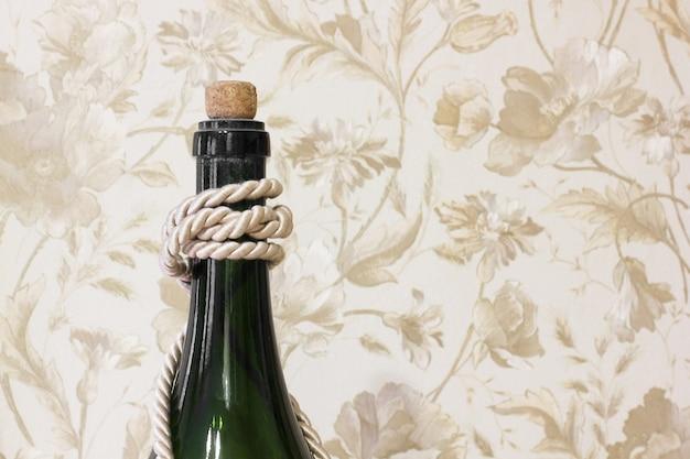 Geschlossener hals der grünen glasflasche auf beige blumenwandmusterhintergrund
