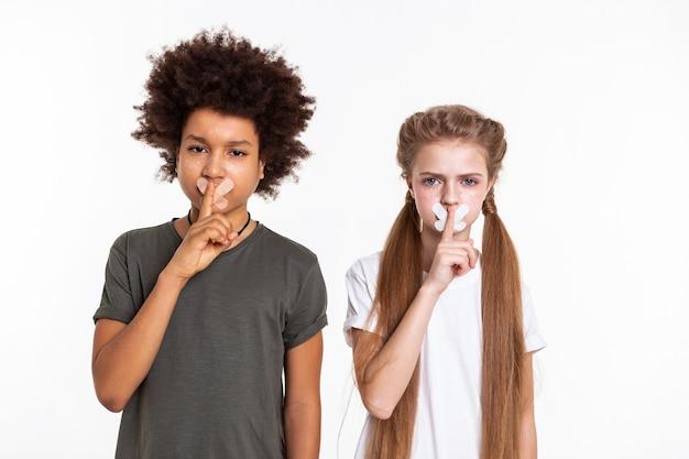 Geschlossener mund. ernsthafte entschlossene kinder, die mit zugeklebten mündern posieren und mit einem finger eine geste der stille zeigen