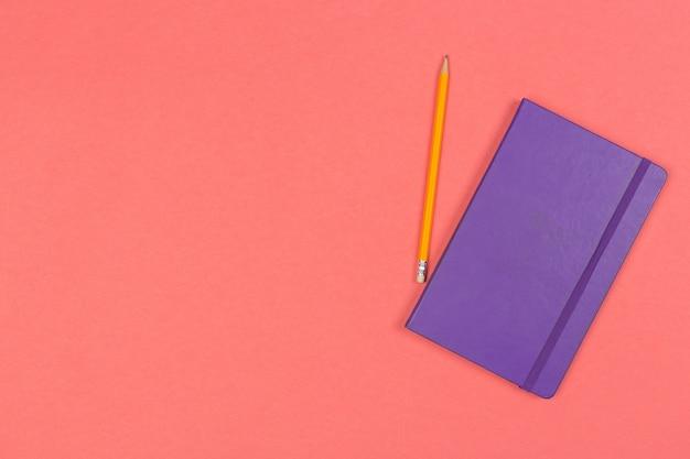 Geschlossener notizblock mit bleistift auf farbiger draufsicht