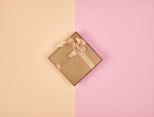Geschlossener quadratischer kasten mit einem bogen auf einem abstrakten farbigen hintergrund
