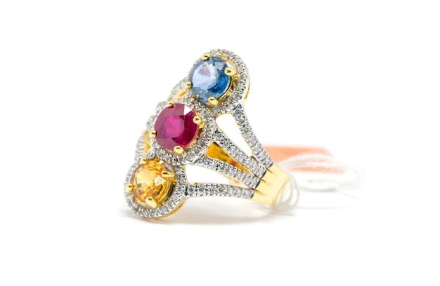 Geschlossener roter, gelber und blauer diamant mit dem weißen diamant- und goldring lokalisiert auf weißem hintergrund