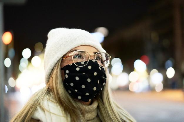 Geschlossener schuss einer jungen blonden frau, die eine maske trägt, die sich nachts in einer stadt umschaut, mit vielen lichtern im hintergrund. winterumgebung.