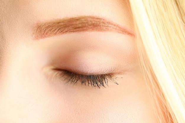 Geschlossenes auge der schönen blonden frau in der morgensonnenschein-nahaufnahme