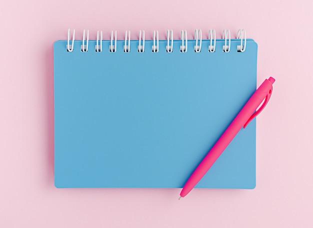 Geschlossenes blaues notizbuch und stift auf rosa hintergrund.