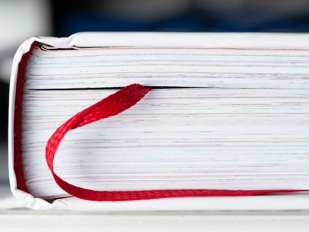 Geschlossenes buch mit einem lesezeichen in form einer roten bandnahaufnahme. das buch ist eine wissensquelle