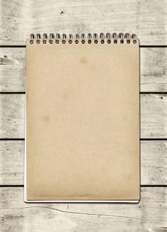 Geschlossenes gewundenes anmerkungsbuch auf einer weißen hölzernen tabelle