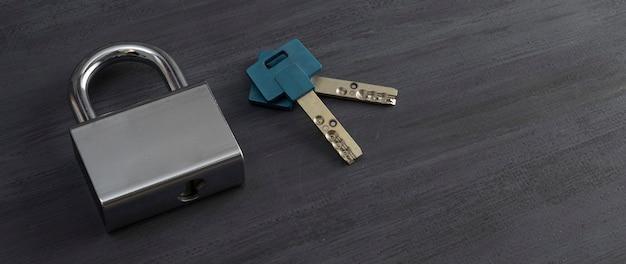 Geschlossenes hochsicherheits-vorhängeschloss silberfarben mit einem satz schlüssel auf grauem hintergrund
