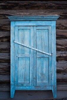 Geschlossenes holzfenster mit fensterläden und geschnitzten mustern an den fenstern in einem rustikalen holzhaus