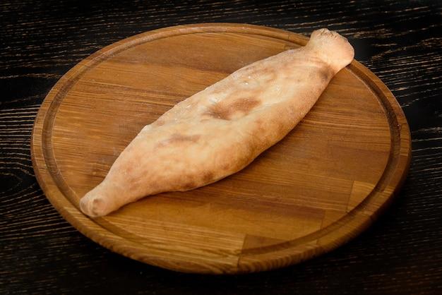Geschlossenes khachapuri mit füllung auf einem holzbrett auf einem dunklen holztisch. georgisches gebäck.