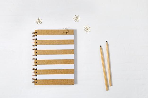 Geschlossenes notizbuch auf frühling mit gold zeichnete abdeckung und hölzernen bleistift auf weißer tabelle. schulheft mit metallklammern. ansicht von oben.