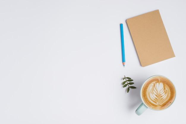 Geschlossenes notizbuch; buntstift; blätter und tasse kaffee mit latte art auf weißem hintergrund