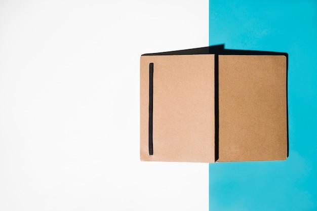 Geschlossenes notizbuch mit brauner bucht auf weißem und blauem hintergrund