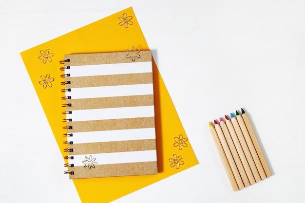Geschlossenes notizbuch und buntstifte zum zeichnen. arbeitsraum für kreative.