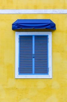 Geschlossenes traditionelles griechisches fenster mit weißem rahmen und blauer gewebemarkise auf gelbem zement