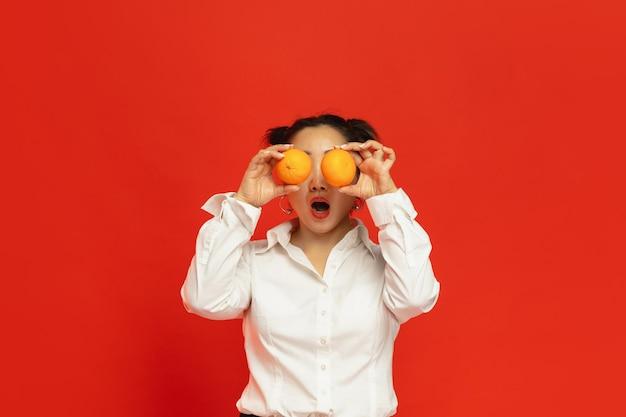 Geschmack der ferien. frohes chinesisches neues jahr 2020. asiatische junge frau, die mandarinen auf rotem hintergrund in traditioneller kleidung hält.