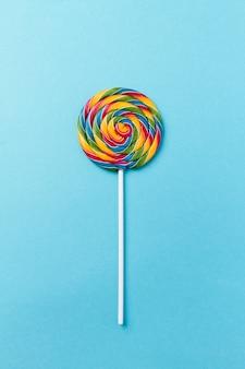 Geschmackvolle appetitliche Party Zubehör Sweet Swirl Süßigkeiten Lollypop auf blauem Hintergrund Draufsicht