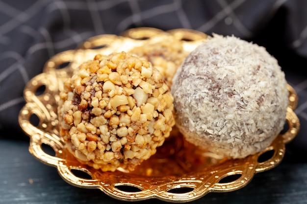 Geschmackvolle ballkuchen oben gedient im goldenen plattenabschluß