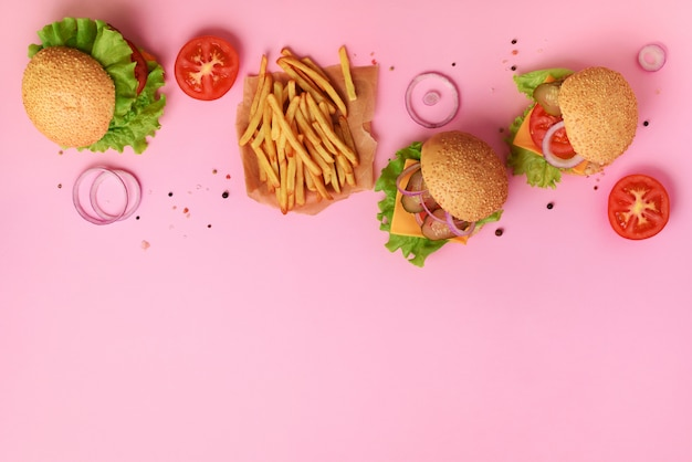 Geschmackvolle burger mit rindfleisch, tomate, käse, zwiebel, gurke und kopfsalat auf rosa hintergrund.