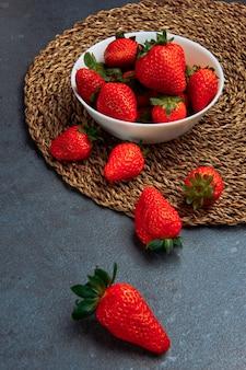 Geschmackvolle erdbeeren in einer hohen winkelansicht der weißen schüssel auf einem grauen und runden tischset-hintergrund