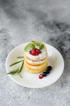 Geschmackvolle frische hüttenkäsepfannkuchen auf einer weißen platte auf einem konkreten hintergrund. gesundes und diätfrühstück