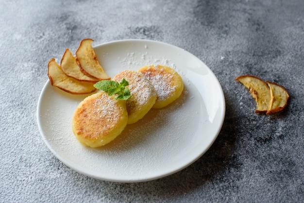 Geschmackvolle frische hüttenkäsepfannkuchen auf einer weißen platte mit einem glas milch auf einem konkreten hintergrund. gesundes und diätfrühstück