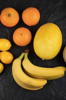 Geschmackvolle frische reife tropische früchte auf schwarzem tisch.