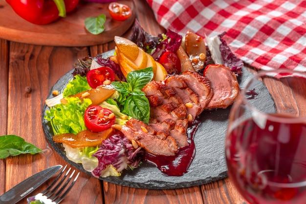 Geschmackvolle geschnittene entenbratenbrust mit frischgemüsesalatnahaufnahme auf einer platte.