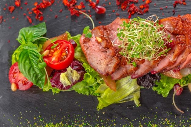 Geschmackvolle geschnittene entenbratenbrust mit frischgemüsesalatnahaufnahme auf einer platte