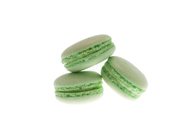 Geschmackvolle grüne makronen getrennt über weißem hintergrund. leckerer snack