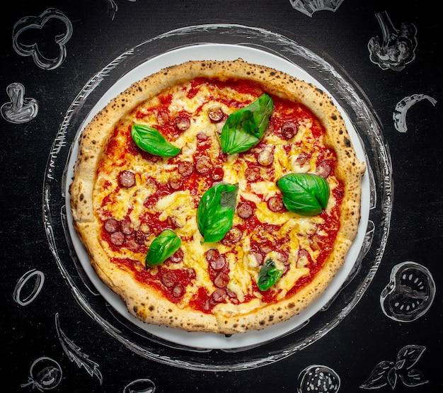 Geschmackvolle italienische pizza mit basilikum auf schwarzem steinhintergrund, draufsicht.